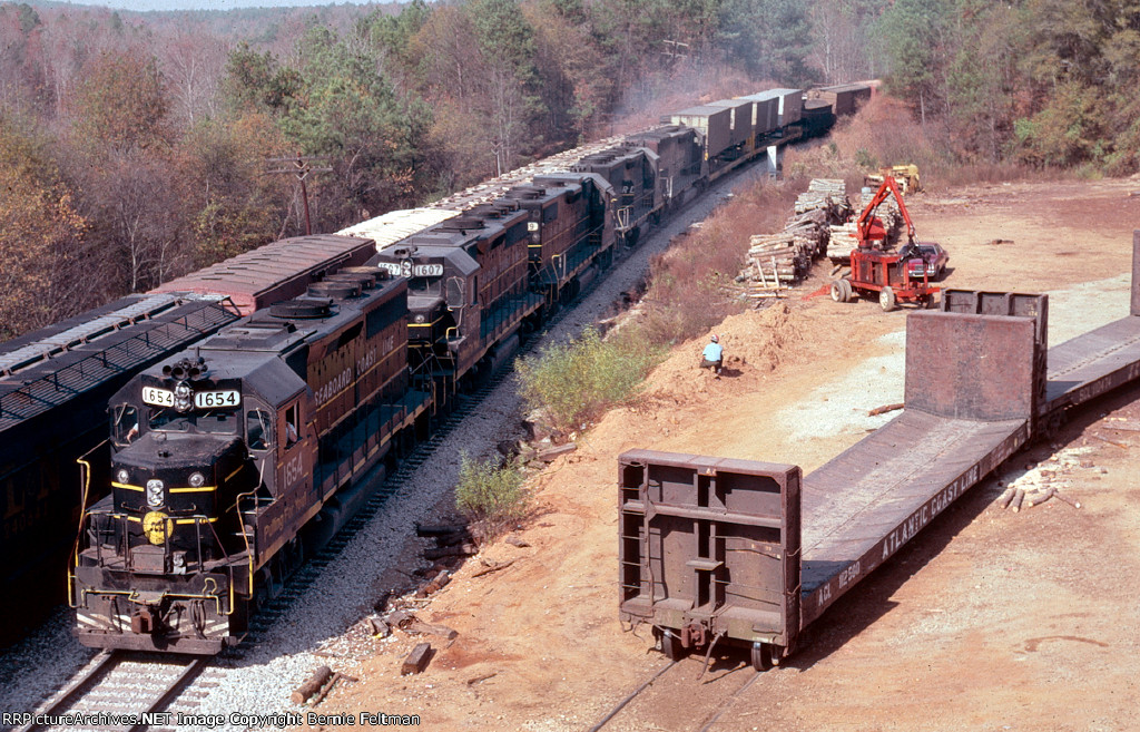 Seaboard Coast Line GP40-2 #1654 leads southbound train #385 (with an SP tunnel motor) meeting train #308 in the siding.  The area of the woodyard in the foreground is the former site of the depot