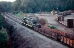 Seaboard Coast Line GP9 #1028, leading a maintenance of way work extra northbound thru the siding, with Cleveland Pulpwood Yard in the background