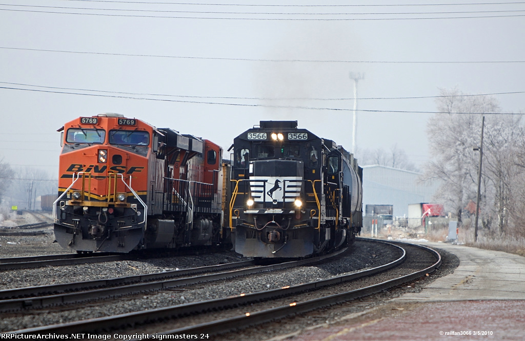 NS 3566 passes a waiting BNSF as it heads out of Elkhart