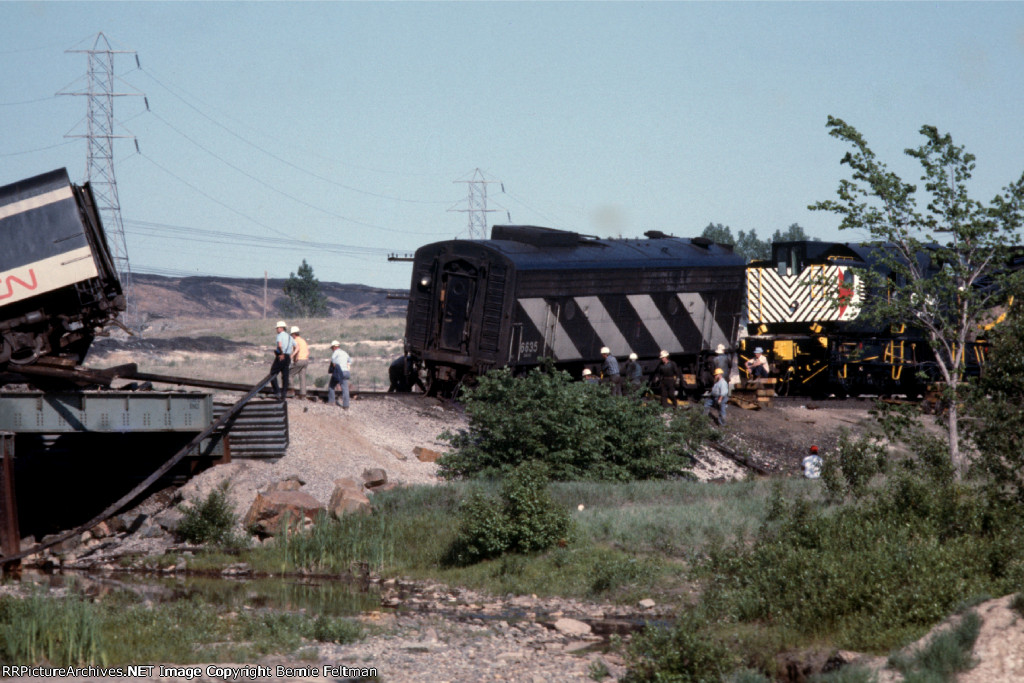 Canadian National F9B #6635, with part of the derailed passenger train it was pulling hanging off the bridge to the left, is in the process of being rerailed by Canadian Pacific Wrecker #414479