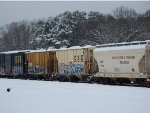 A LINE OF FREIGHT CARS IN A SNOW COVERED RAILROAD YARD