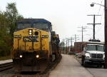 Q163 rolls past some railfans and parked CSX trucks