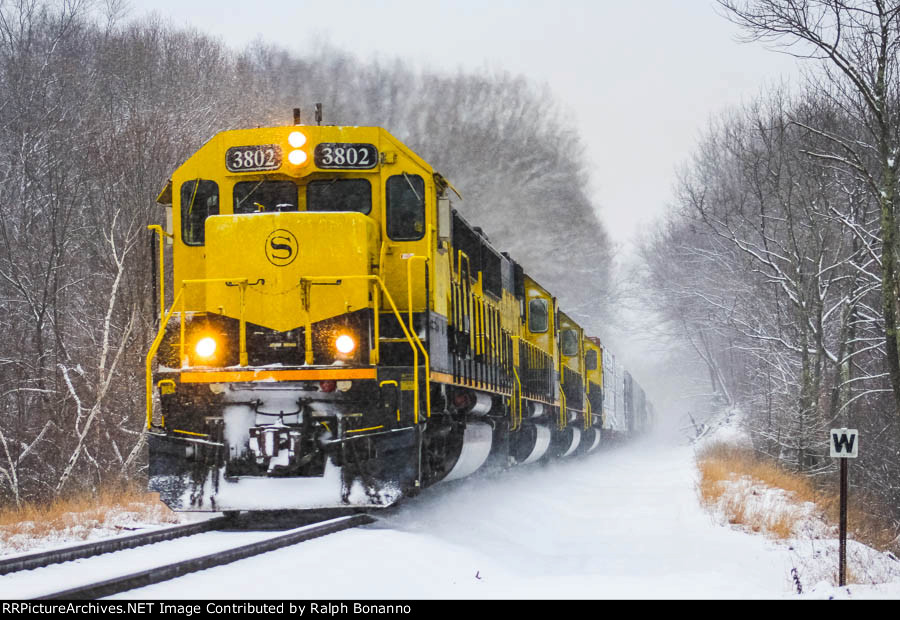 As the snow tapers off, SU 99 crests the westbound grade of Sparta Mountain