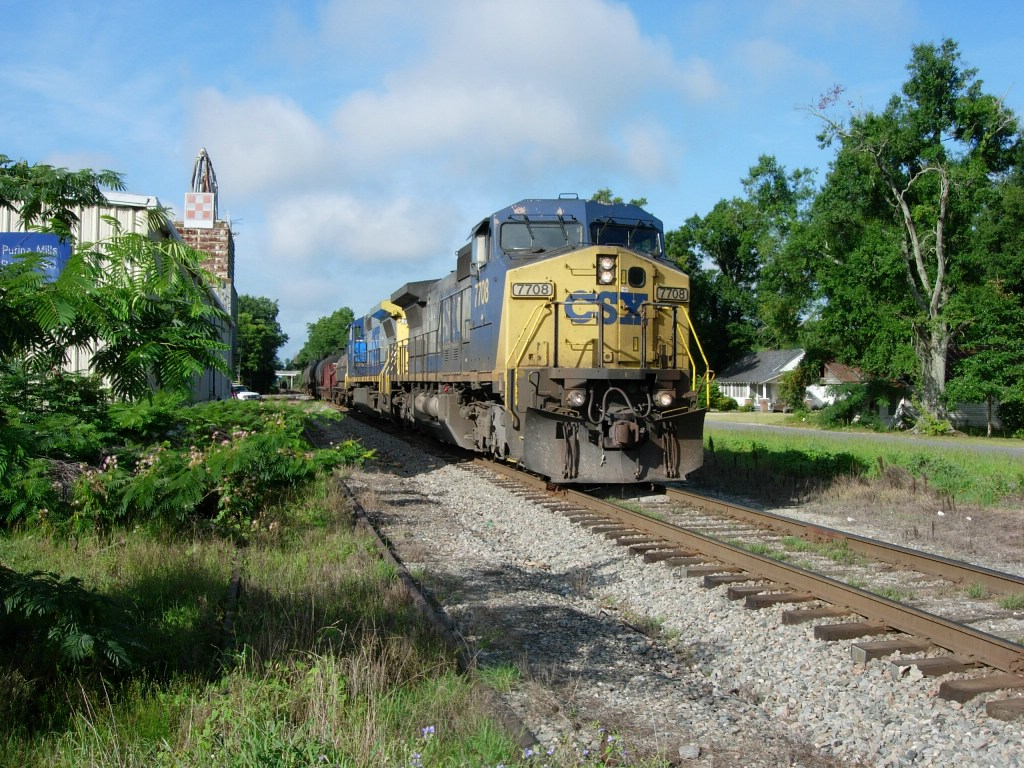 CSX trains passes an abandonded side track next to Purina Mills building