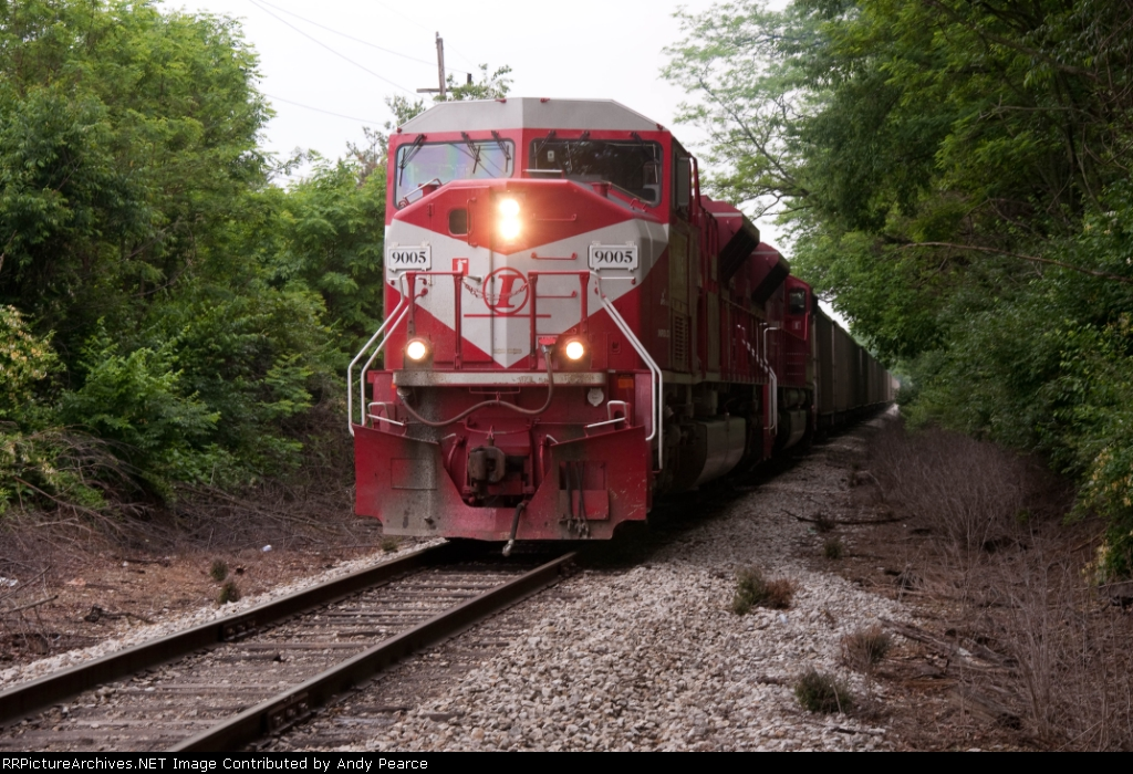 First shot. On light jointed rail the train crosses Pete Ellis Drive,