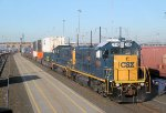 A pair of CSX's 4 axle gen set locomotive move intermodal cars around in the yard on a sunny morning