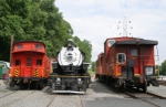 Cabooses surround a steam locomotive