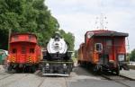 Cabooses surround a steam locomotive