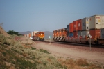 BNSF 7854 rolling east passes BNSF 7802 rolling west as they pass each other just west of BNSF Barstow yard in Lenwood, Ca.