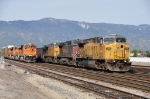 UP 7306 (AC4460CW) leads a coal train past a waiting BNSF freight at Reana CA. 3/14/2010
