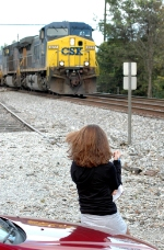 A young female railfan looks on as a Southbound loaded coal train passes