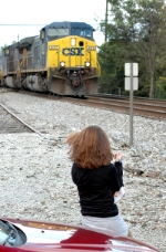 A young female railfan looks on as a CSX Southbound loaded hopper train rolls by.