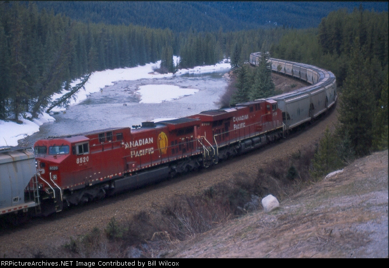 CP 8735 & 8520 work as mid-train helpers on a westbound CANPOTEX train along the Bow River around Morant's Curve, east of