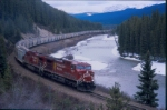 CP 9835 & 9827 lead a westbound CANPOTEX train along the Bow River around Morant's Curve, east of