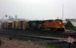 BNSF 5446 heads north in a rain storm with an eastern visitor