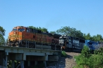 BNSF 4607, GE C44-9W, and NS 7146, EMD GP60, crossing a creek with a westbound manifest