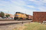 Freight train pops out from behind a building