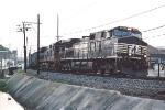 Eastbound coal train rolls past shops