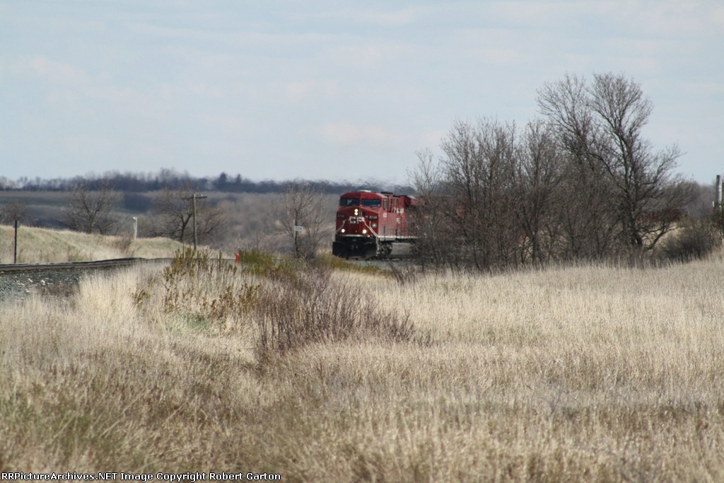 CP 8728 Emerges From Behind Some Trees While Climbing Out of the Des Lacs Valley
