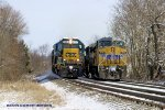 CSX 8305 leads Q275 past empty Q237 tied down on the siding