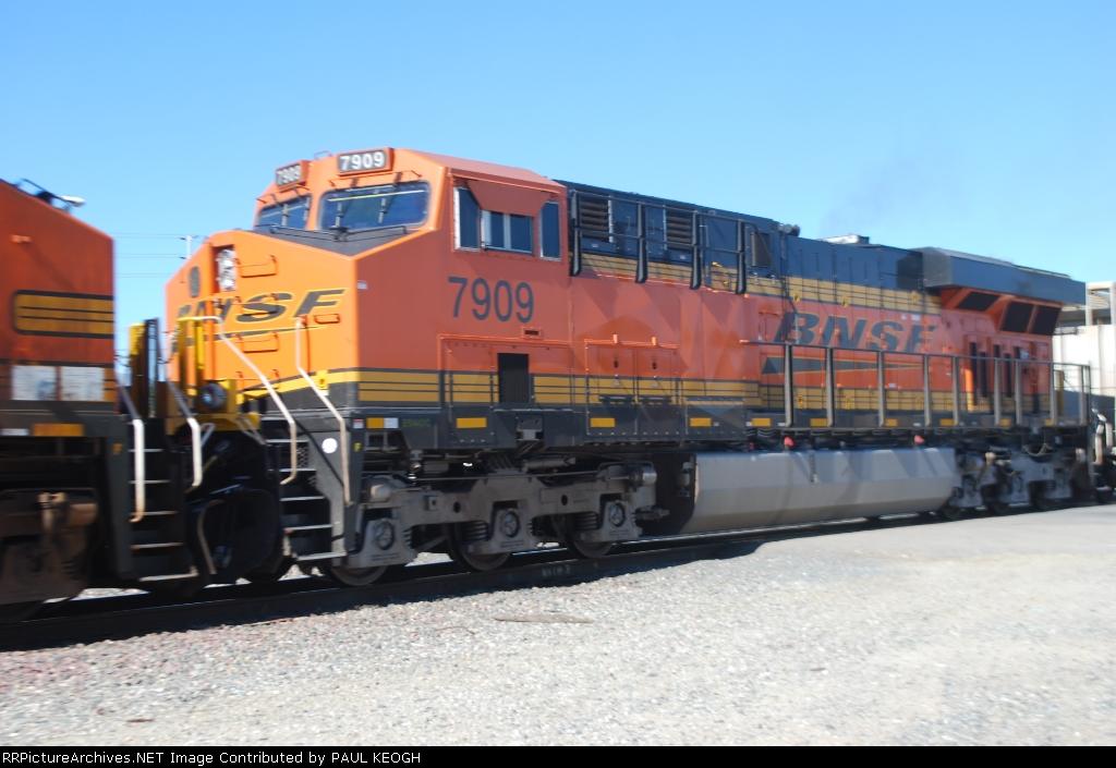BNSF 7909 heads west as the # 3 unit on a manifest train.