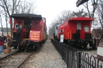 The M&E's caboose sits abreast of the Maywood Station's preserved former Conrail caboose while taking donations