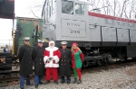 """The 3 Marines who rode the train, Santa Claus, and his """"elf"""" pose in front of the NYS&W preserved S2 # 206"""
