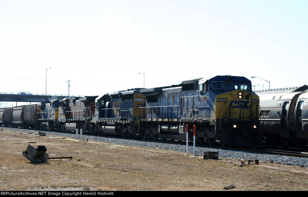 CSX 7792 leads a northbound grain train past train P092, stopped at the station