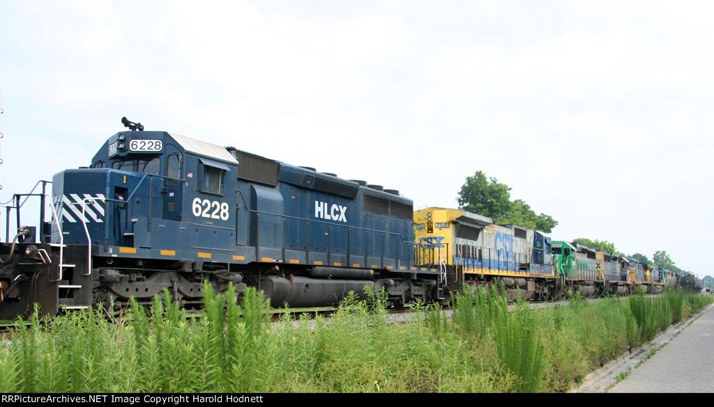 HLCX 6228 is the last of 8 locos on an empty grain train