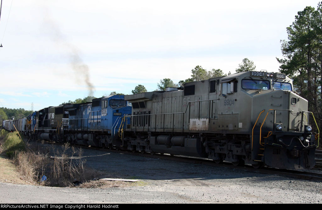 NS 9904 leads a train out of the yard