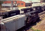 NS 4163 shoves cars while a string of SD's pulls a grain train out of the siding