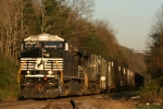 NS 7701 leads a string of empty chip cars eastbound