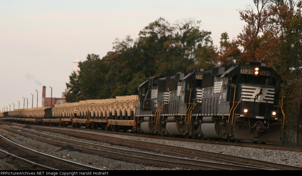 NS 7129 leads train 350 through town with some military loads