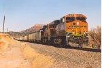 Loaded coal train climbs uphill