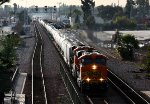 A BNSF mixed freight rolls south while a Metrolink approaches