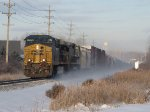 Q334-09 kicks up a cloud of snow as it heads rolls into the morning sun