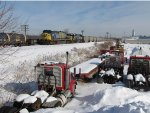 Four trucks sit buried in the snow as N911-08 rolls past