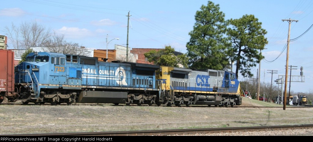 CSX 7323 & 7885 head towards the yard as another train waits to leave
