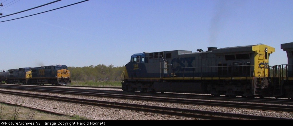 CSX 146 leads a train on the inbound lead past an outbound train