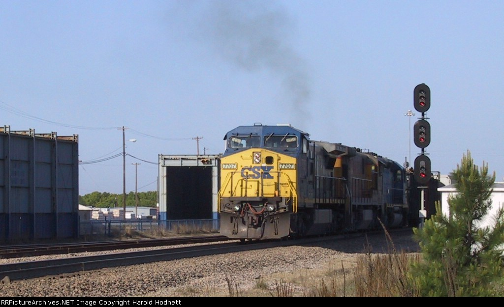CSX 7707 leads a train northbound past the signals
