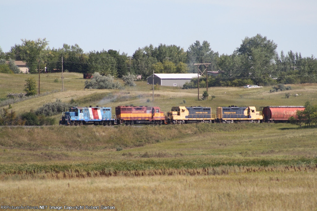 A Mix of EMD Power in Former Owners' Livery Take a String of Grain Hoppers East on the Former SOO Wheat Line