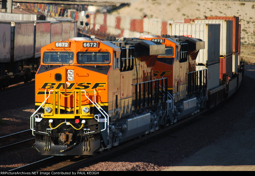 BNSF 6672 and BNSF 6673 Brand New Locomotives Push a Eastbound Z-Train as the Setting Sun Reflects off their BNSF Swoosh Logo and the Exhaust from their Exhaust stacks blur the picture off the Z-Train as it passes under Hwy 58,