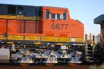 BNSF 6677 side shot as she passes me by doing about 45 MPH as the Rising Sun Reflects off Her Brand New Swoosh Logo Paint.