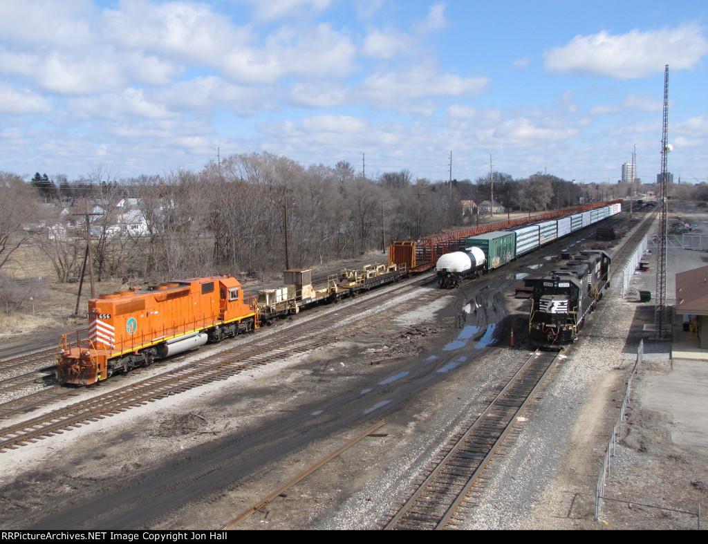 A CN rail train waits in the yard as NS's B55 power sits nearby