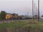 Dirty dirt train K253 heads west at dusk