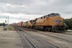 An overcast sky prevails as an eastbound stack enters town, on the approach for Proviso yard
