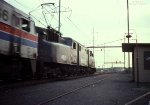 Amtrak GG-1 #4911 lends a hand to an ailing E-60 (#966) hauling a westbound through the station at Frankford Junction in Philadelphia, PA. May 15, 1979