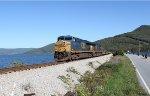 CSX 5412 highballs along the shore of lake Nickajack with a baretable train