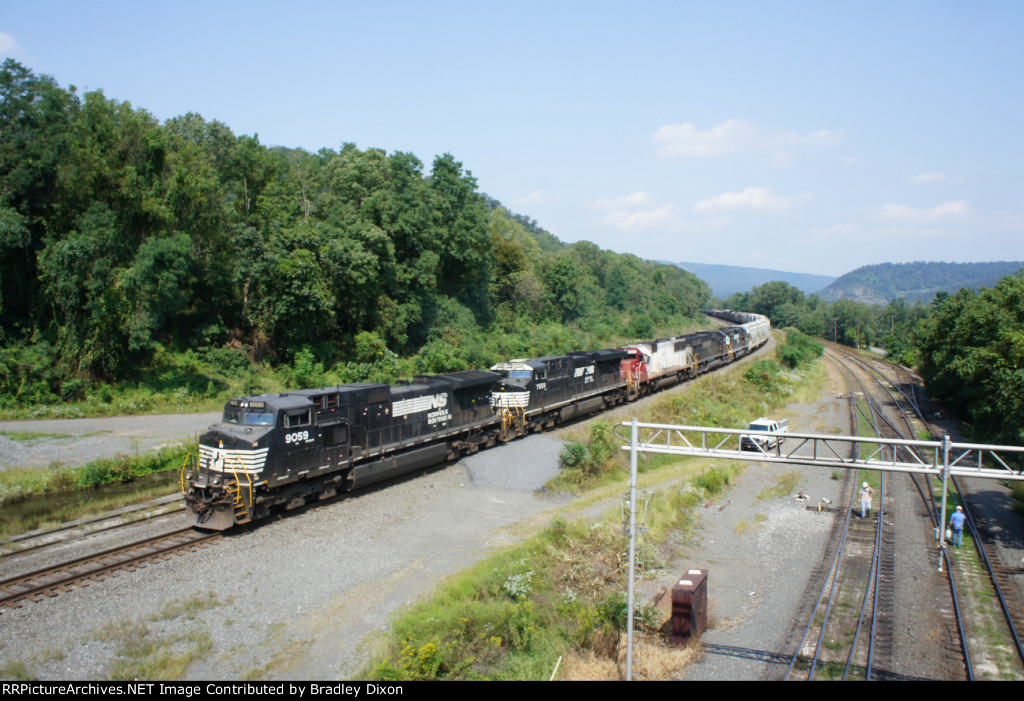 NS 9059 coming into enola yard while NS worker spay weed