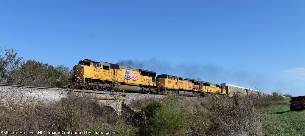 UP 4761 is smoking while heading west.
